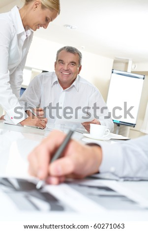 Portrait of happy boss looking at one of workers during office work - stock photo