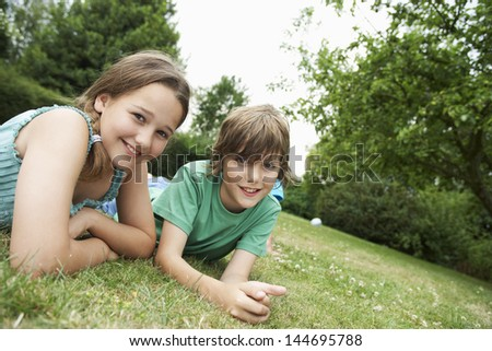 Portrait of happy boy and girl lying in grass - stock photo