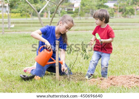 Portrait of Happy Boy and Girl Watering Plants Outdoors