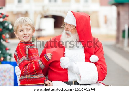 Portrait of happy boy giving letter to Santa Claus in courtyard - stock photo
