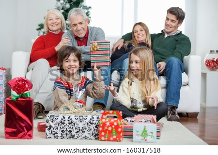 Portrait of happy boy holding Christmas gift with family sitting in house - stock photo