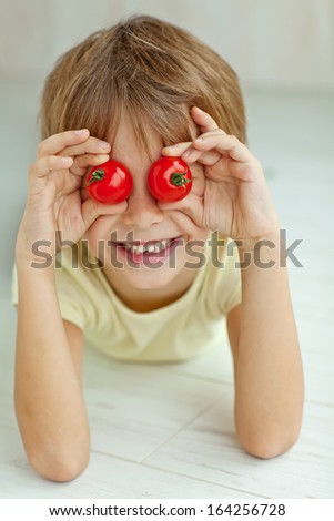 Portrait of happy boy holding ripe tomatoes before his eyes - stock photo