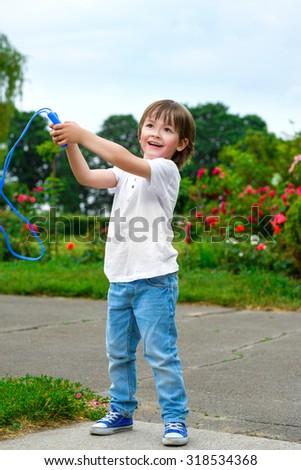Portrait of happy boy holding skipping rope - stock photo
