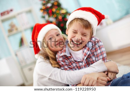 Portrait of happy boy laughing in his sister embrace on Christmas evening - stock photo