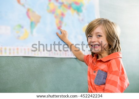 Portrait of happy boy pointing on map in classroom - stock photo