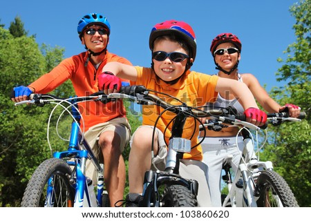 Portrait of happy boy riding bicycle in the park with his parents behind - stock photo