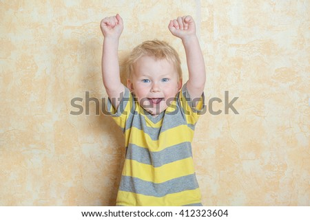 Portrait of happy boy showing hands up gesture. laughing happy boy jumping with raised hands up - stock photo
