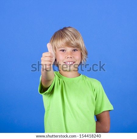Portrait of happy boy showing thumbs up gesture - stock photo