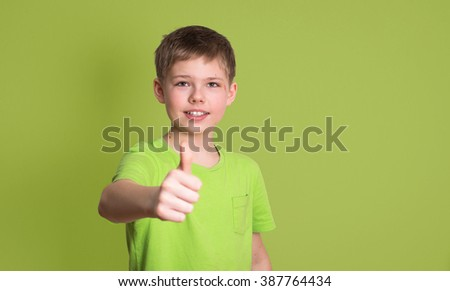 Portrait of happy boy showing thumbs up gesture, isolated over green background. - stock photo