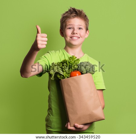Portrait of happy boy showing thumbs up gesture, isolated over green background. Laughing kid holding paper shopping bag full of fresh organic fruit, vegetables and greens. Healthy eating concept. - stock photo
