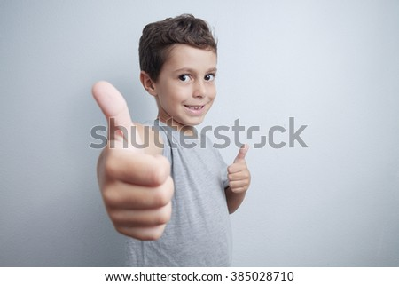 Portrait of happy boy showing thumbs up gesture, on gray background - stock photo