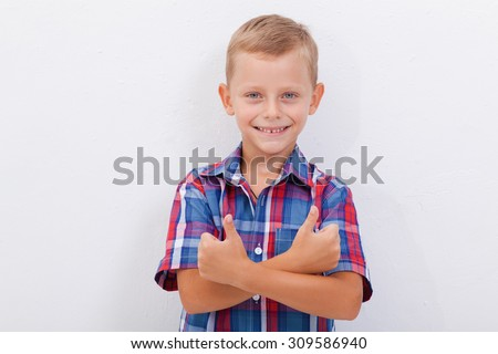 Portrait of happy boy showing thumbs up gesture,  over white background - stock photo