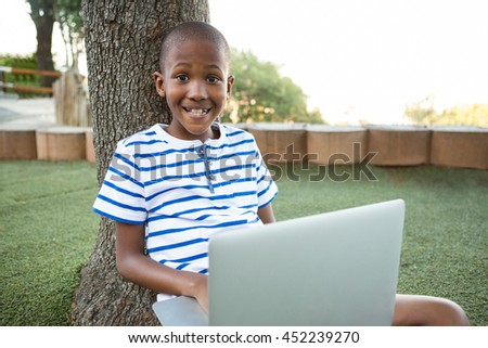 Portrait of happy boy using laptop while sitting at park