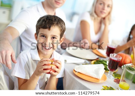 Portrait of happy boy with apple sitting at festive table and looking at camera with his family on background - stock photo