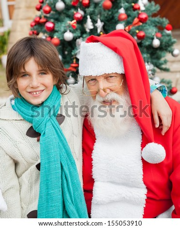 Portrait of happy boy with arm around Santa Claus against Christmas tree - stock photo