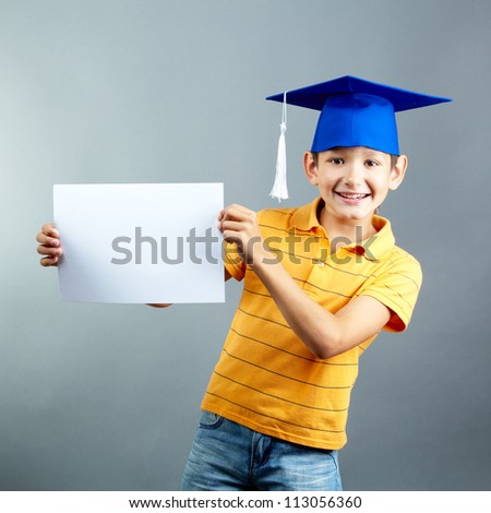 Portrait of happy boy with blank paper looking at camera - stock photo