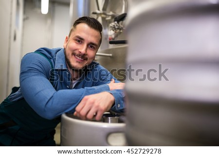 Portrait of happy brewer leaning on keg at brewery