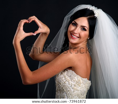 Portrait of happy bride in beautiful dress making shape of heart with her hands on black background