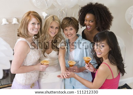 Portrait of happy bridge celebrating party with her mother and friends - stock photo