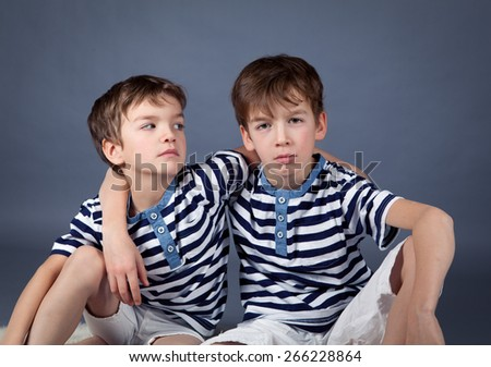 Portrait of happy brothers in studio on  gray background - stock photo
