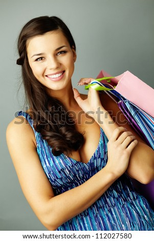 Portrait of happy brunette after shopping looking at camera - stock photo