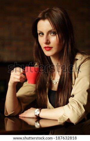 Portrait of happy brunette drinking a cup of coffee - stock photo