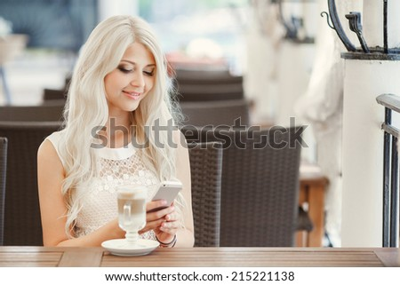 Portrait of happy brunette with mug in hands. pretty young woman sitting in the cafe with a cup of tea - stock photo
