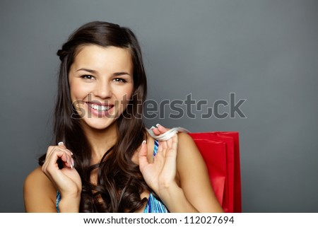 Portrait of happy brunette with paperbag looking at camera - stock photo