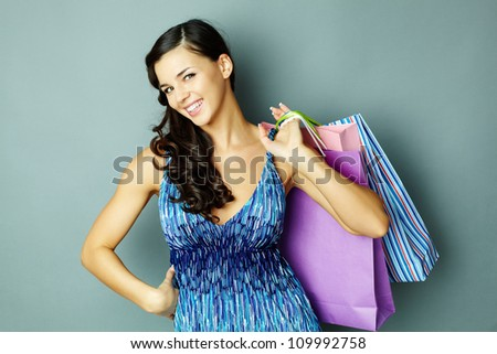 Portrait of happy brunette with paperbags looking at camera with smile - stock photo