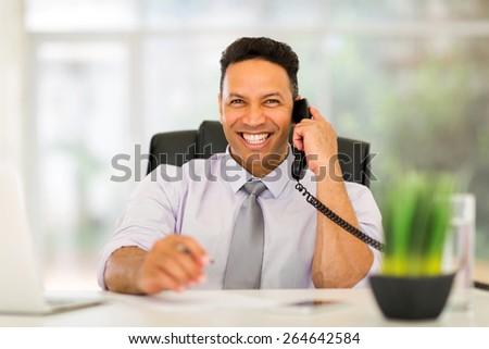 portrait of happy business executive talking on landline - stock photo