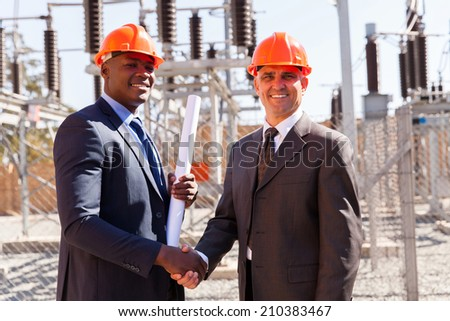 portrait of happy business partners handshaking at electrical power station