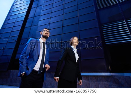 Portrait of happy business partners walking on background of modern building - stock photo