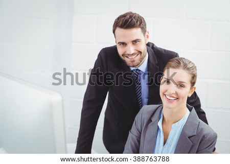 Portrait of happy business people at computer desk in office