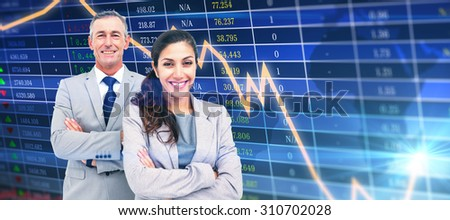 Portrait of happy business people standing together against stocks and shares - stock photo