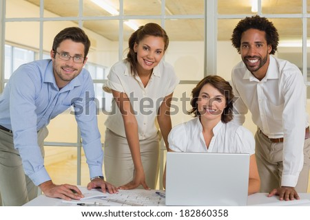 Portrait of happy business people using laptop in meeting at the office - stock photo