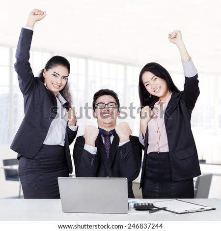 Portrait of happy business team celebrating their triumph in the office by raising their hands - stock photo