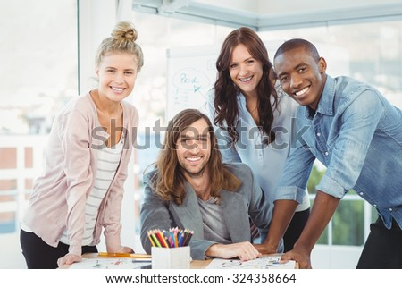 Portrait of happy business team discussing at desk in creative office - stock photo