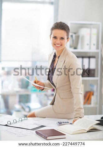 Portrait of happy business woman working in office - stock photo