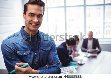 Portrait of happy businessman against as colleagues in meeting room at creative office - stock photo