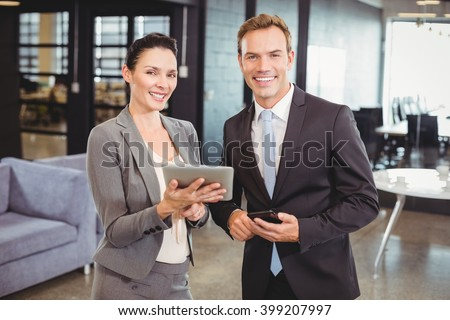 Portrait of happy businessman and businesswoman with digital tablet and mobile phone