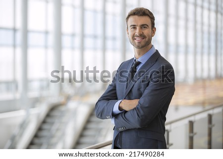Portrait of happy businessman at an airport terminal - stock photo