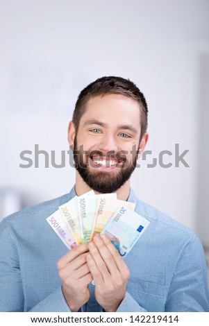 Portrait of happy businessman holding Euro notes in office - stock photo
