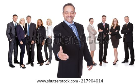 Portrait of happy businessman offering handshake and his team. Isolated on white - stock photo