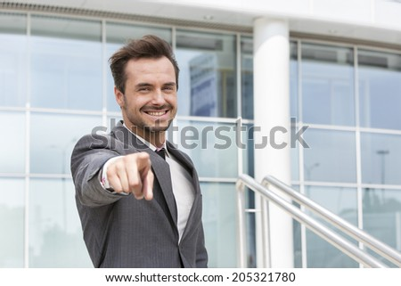 Portrait of happy businessman pointing at you outside office building - stock photo