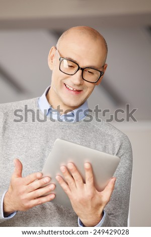 Portrait of happy businessman presenting his idea, while holding digital tablet and standing at office.  - stock photo