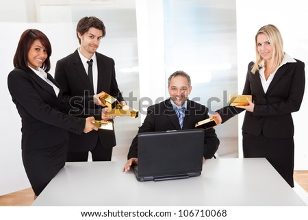 Portrait of happy businessman receiving gold bars - stock photo