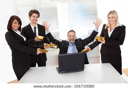 Portrait of happy businessman receiving gold bars