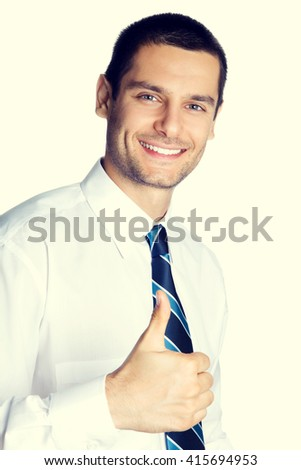 Portrait of happy businessman showing thumbs up hand sign gesture. Caucasian male model at studio shot. Business and success concept.