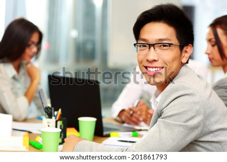 Portrait of happy businessman sitting in front of colleagues