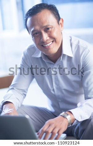 Portrait of happy businessman sitting with laptop and looking at camera - stock photo